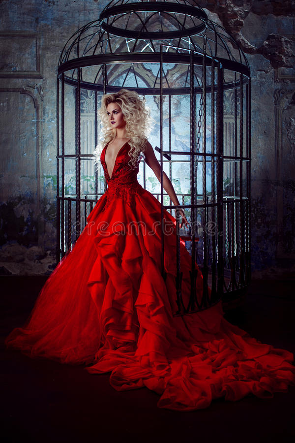 Fashion blonde in red dress with fluffy skirt near the birdcage, concept of liberation stock photos