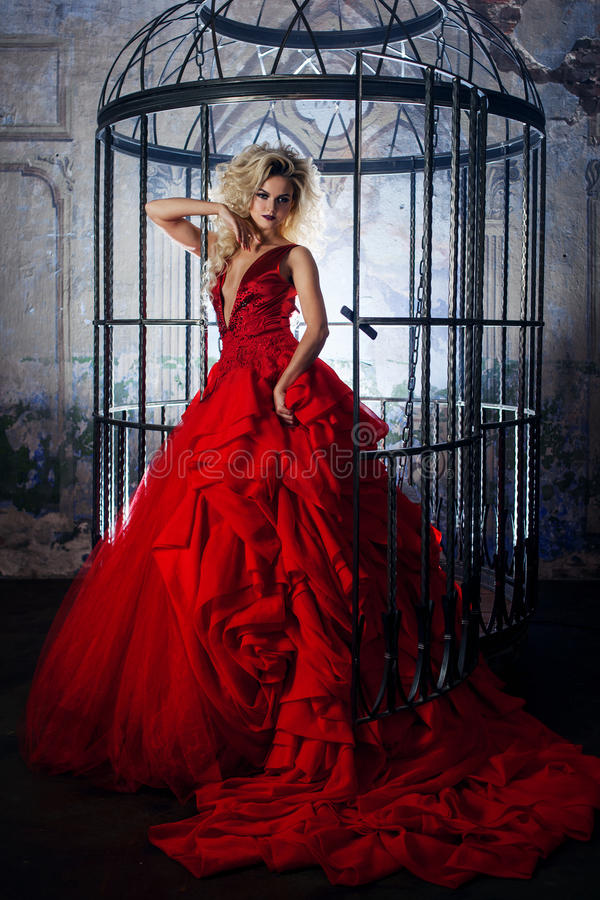 Fashion blonde in red dress with fluffy skirt near the birdcage, concept of liberation stock image