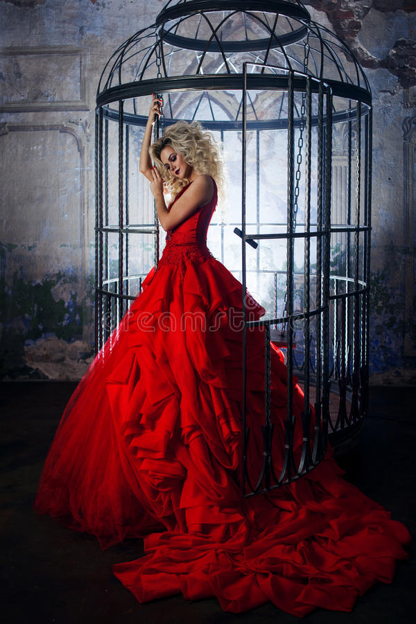 Fashion blonde in red dress with fluffy skirt near the birdcage, concept of liberation stock photography