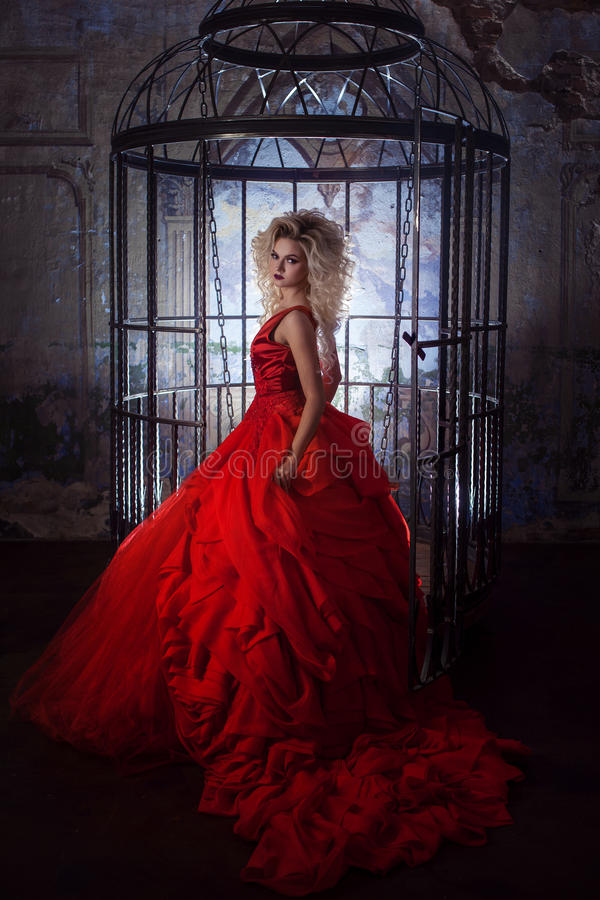 Fashion blonde in red dress with fluffy skirt near the birdcage, concept of liberation royalty free stock photo