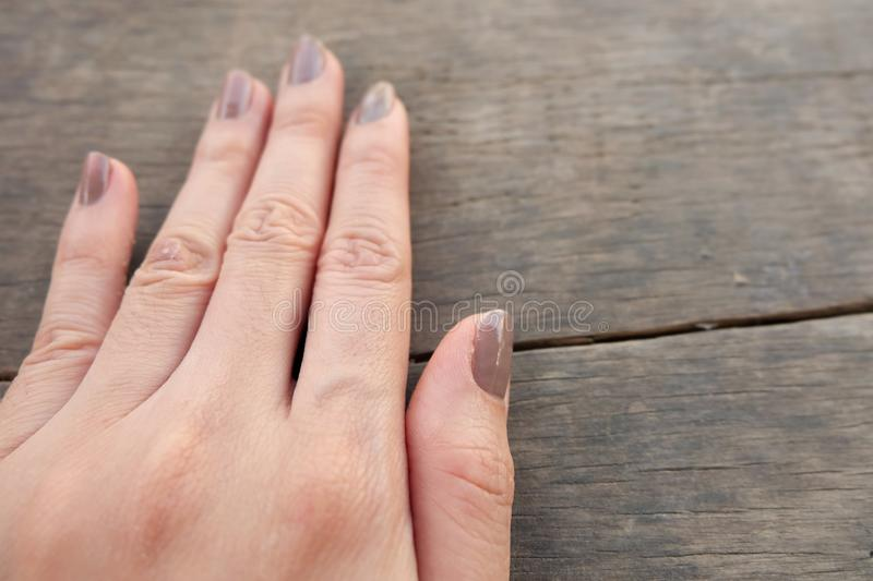 Fashion Brown Manicure Nail. Female's Hand Nails Polish on the Wood Background. Great for Any Use stock photography