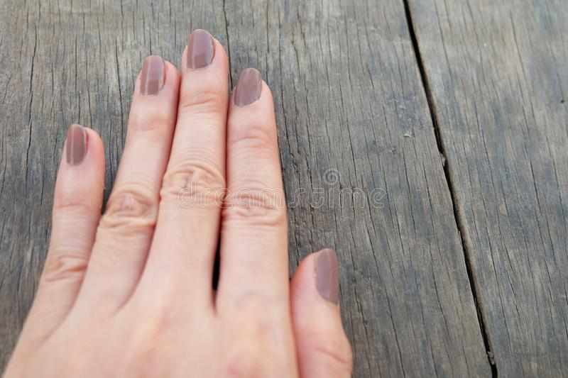 Fashion Brown Manicure Nail. Female's Hand Nails Polish on the Wood Background. Great for Any Use stock image