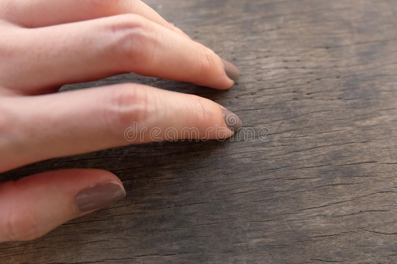Fashion Brown Manicure Nail. Female's Hand Nails Polish on the Wood Background. Great for Any Use royalty free stock photos