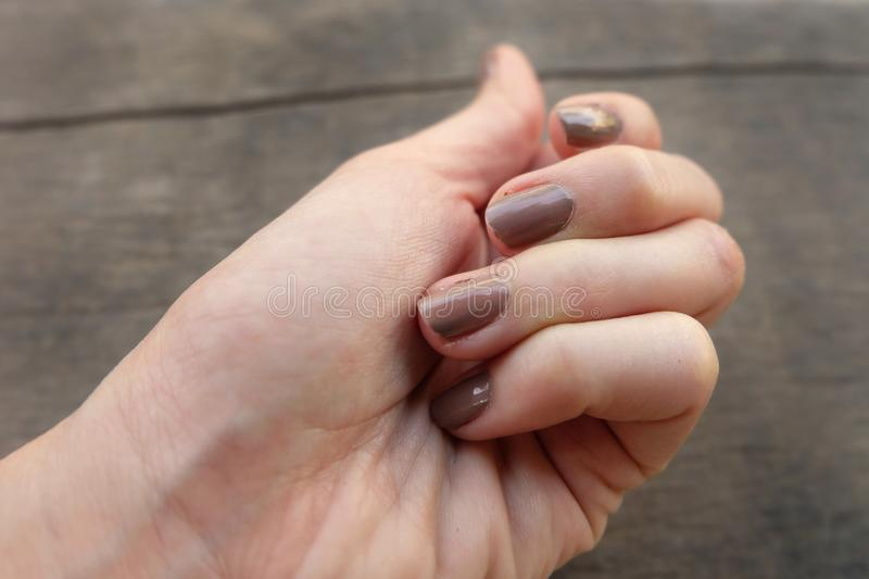 Fashion Brown Manicure Nail. Female's Hand Nails Polish on the Wood Background. Great for Any Use stock images