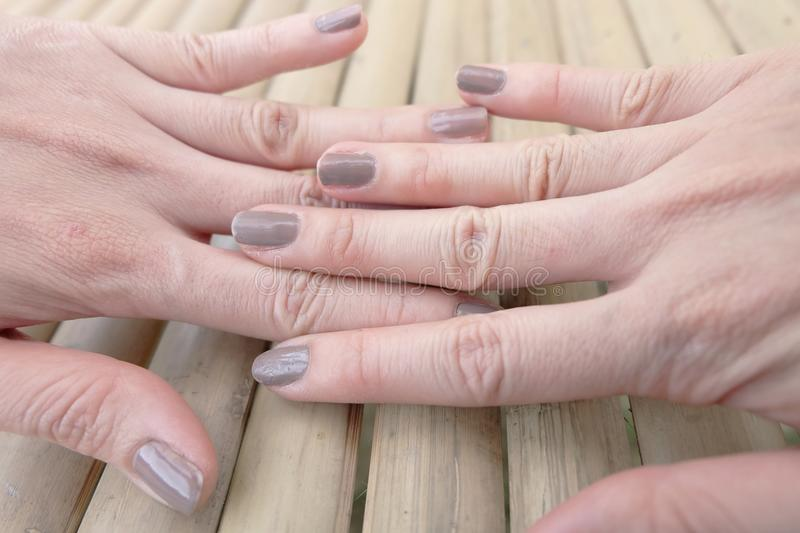 Fashion Brown Manicure Nail. Female's Hand Nails Polish on the Wood Background. Great for Any Use stock photos