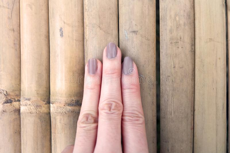 Fashion Brown Manicure Nail. Female's Hand Nails Polish on the Wood Background. Great for Any Use royalty free stock image