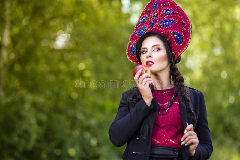 Fashion Brunete Woman In Russian Style Kokoshnik Outdoors Against Nature Background. Posing With Apple. Horizontal Image stock image