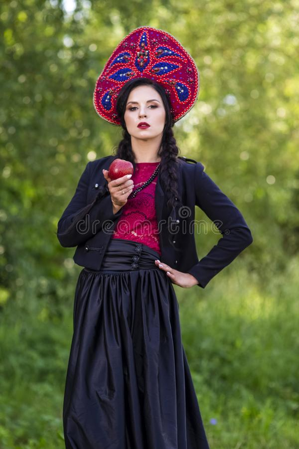 Fashion Brunete Woman In Russian Style Kokoshnik Outdoors Against Nature Background. Posing With Apple. Vertical Shot royalty free stock photo