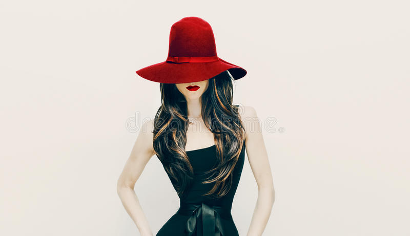 Fashion brunette lady in red hat and red lips on white background stock photo