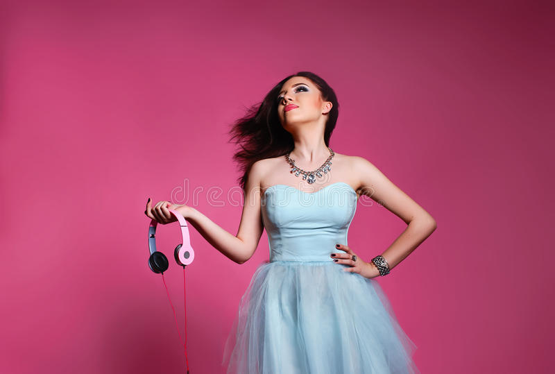 Fashion brunette over pink background. girl in a blue dress with headphones stock photos