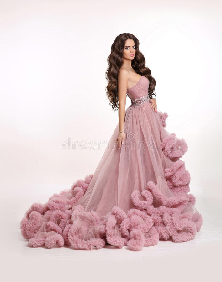 Fashion brunette woman in gorgeous long pink dress posing isolated on white studio background. Beautiful Lady in luxury lush gown. stock image