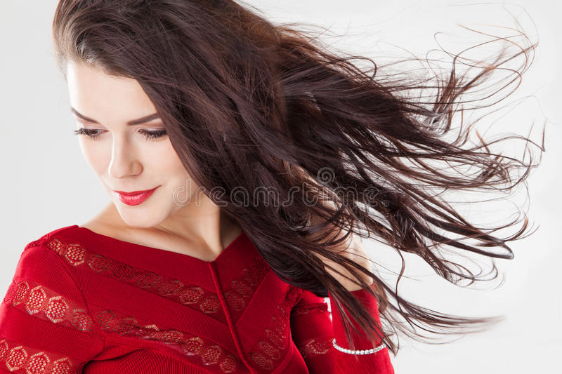 Fashion brunette woman with long hair fluttering in the wind stock image