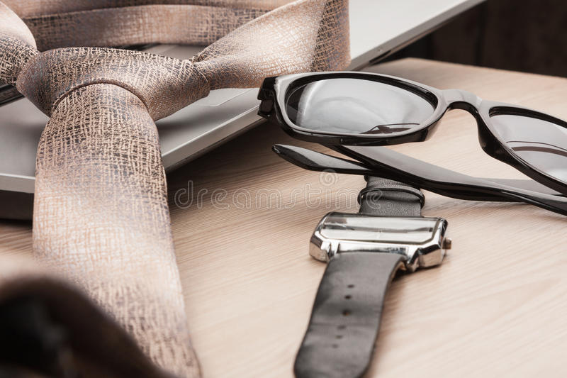 Fashion and business. Close-up sunglasses, tie and watch, on a wooden table. As background stock photos