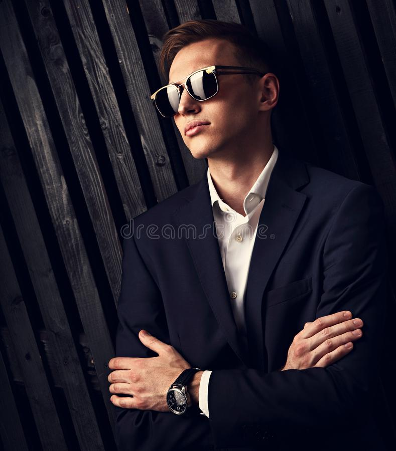 Fashion business man in suit posing in trendy eyeglasses and watches on the hand with folded arms on black studio wooden royalty free stock photo