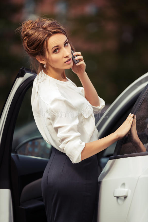 Fashion business woman calling on mobile phone beside a car royalty free stock photography
