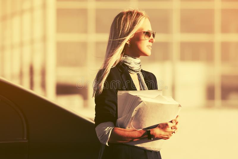 Fashion business woman with financial papers next to her car. Stylish female model wearing black blazer and sunglasses stock photos