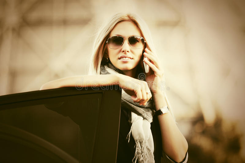 Fashion business woman in sunglasses talking on cell phone next to car stock photos