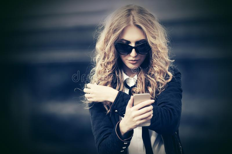 Fashion business woman in sunglasses using smart phone on city street stock photography