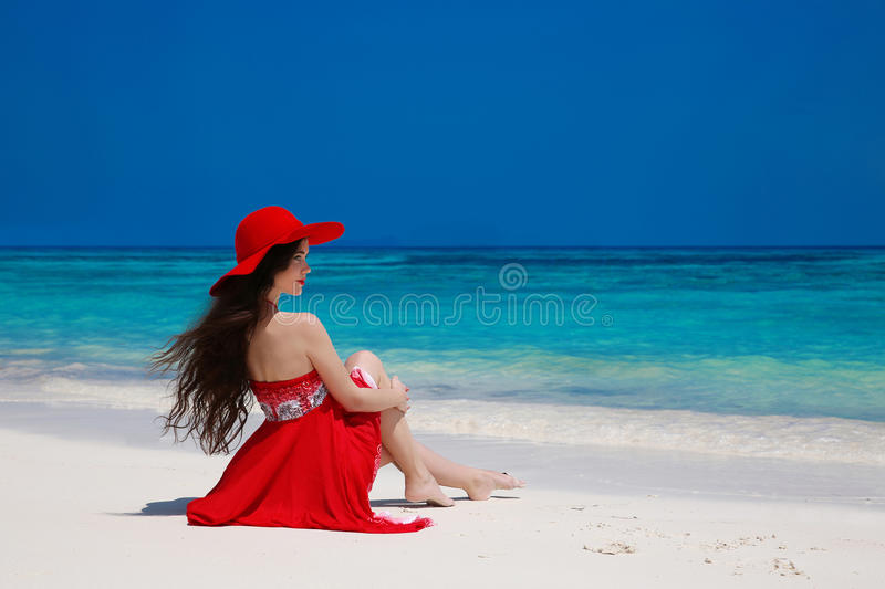 Fashion carefree woman in hat enjoying exotic sea, brunette relax on tropical beach at summer holiday. Attractive girl in red royalty free stock photography