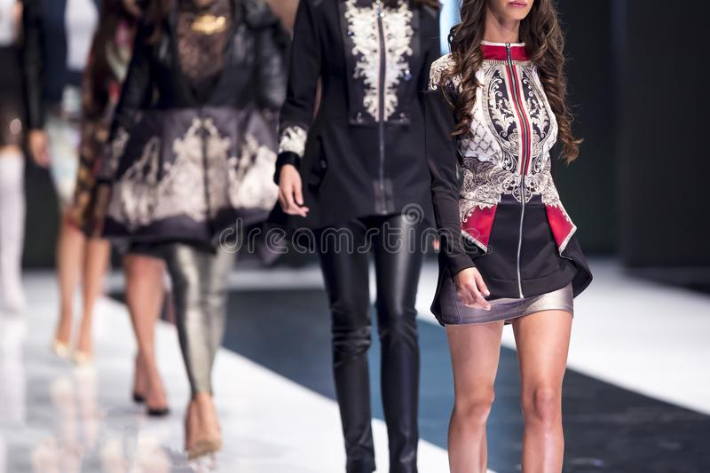 Fashion catwalk runway show models. Female models walk the runway in different dresses during a Fashion Show. Fashion catwalk event showing new collection of royalty free stock images