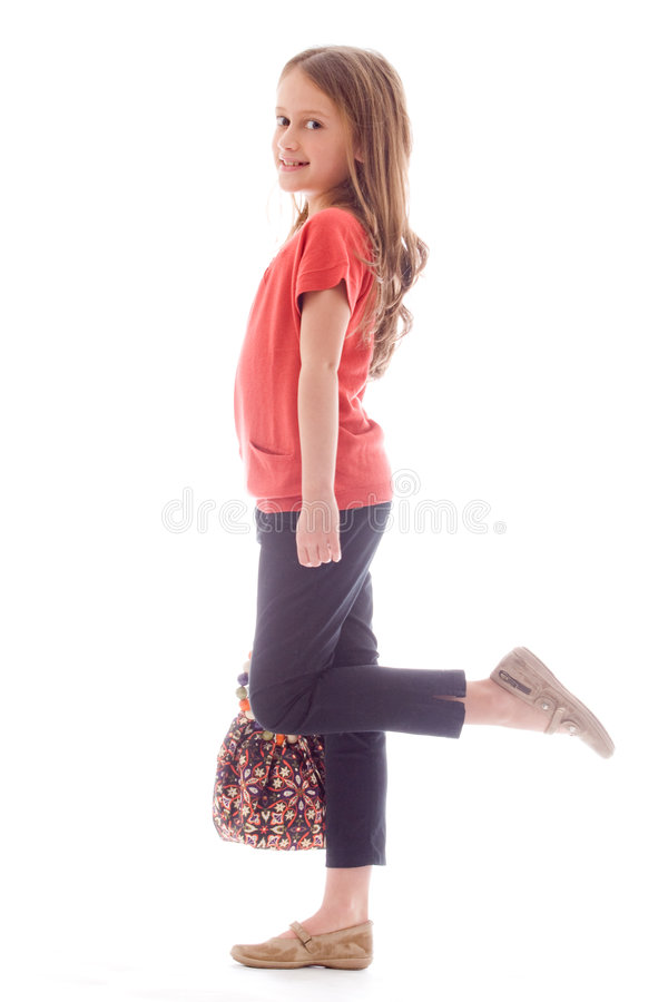 Fashion child with a leg up. Young brunette child posing in different clothes stock image