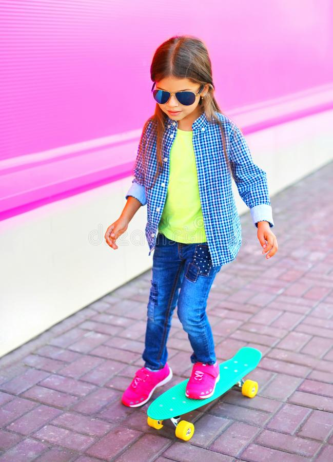 Fashion child little girl on skateboard on colorful pink wall royalty free stock photography