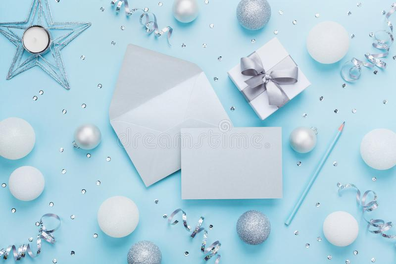 Fashion christmas mockup for greeting. Envelope, paper card, gift box and decoration on blue table top view. Flat lay style. Fashion christmas mockup for stock photo