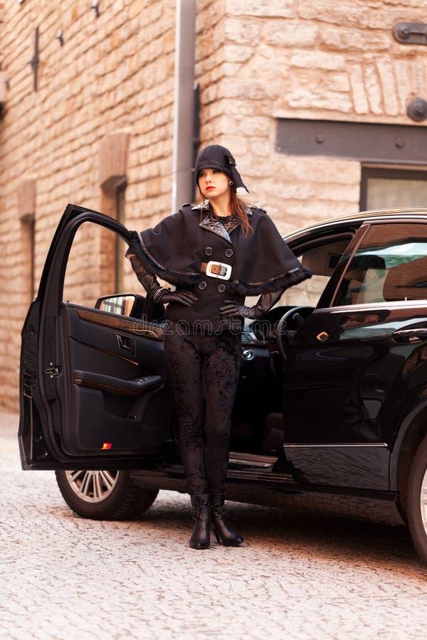 Fashion city life. Elegant woman posing near the luxury car stock images