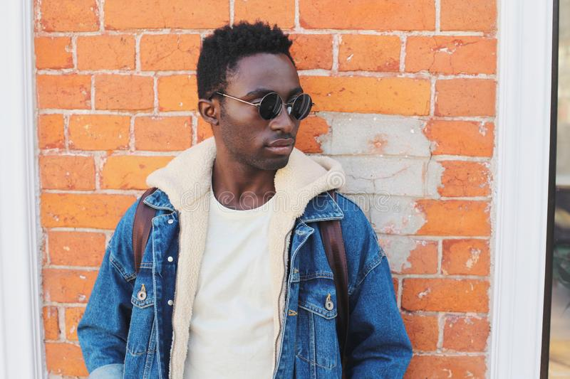 Fashion close-up portrait african man wearing jeans jacket, black sunglasses on city street over brick wall. Background royalty free stock images