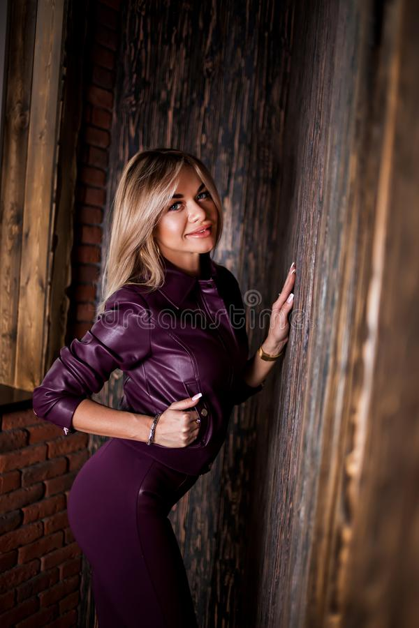 Fashion close up portrait of pretty, stylish woman in purple leather jacket with hand in pocket cute smiling looking down. Spring royalty free stock photography