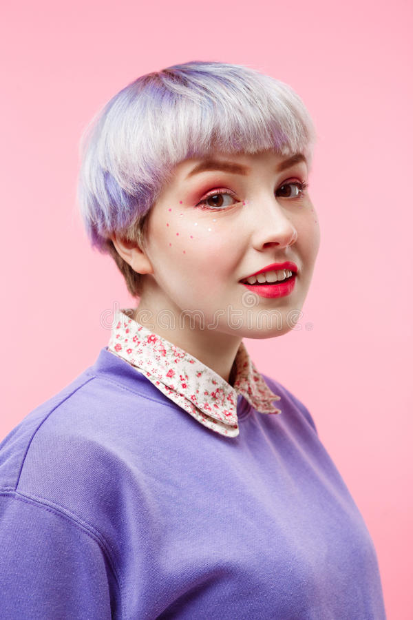 Fashion close-up portrait of smiling beautiful dollish girl with short light violet hair wearing lilac sweater over pink royalty free stock images