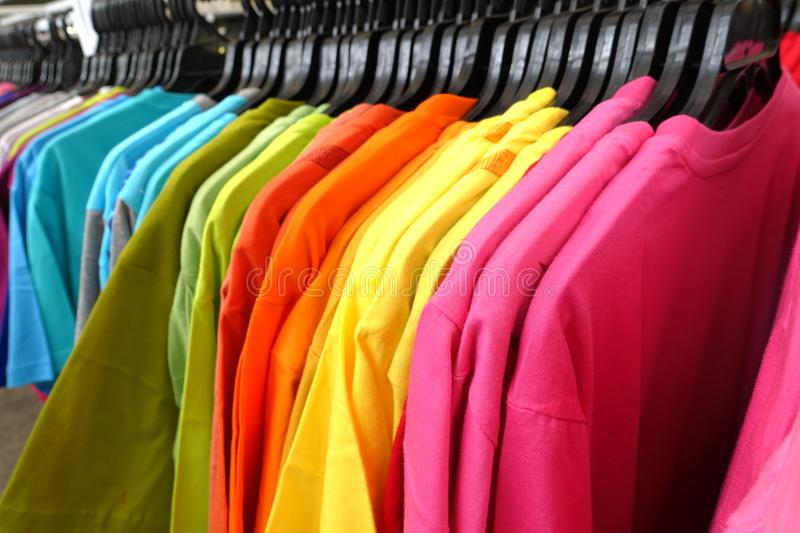 Fashion clothes on clothing rack - bright colorful closet. Close-up of rainbow color choice of trendy female wear stock photos