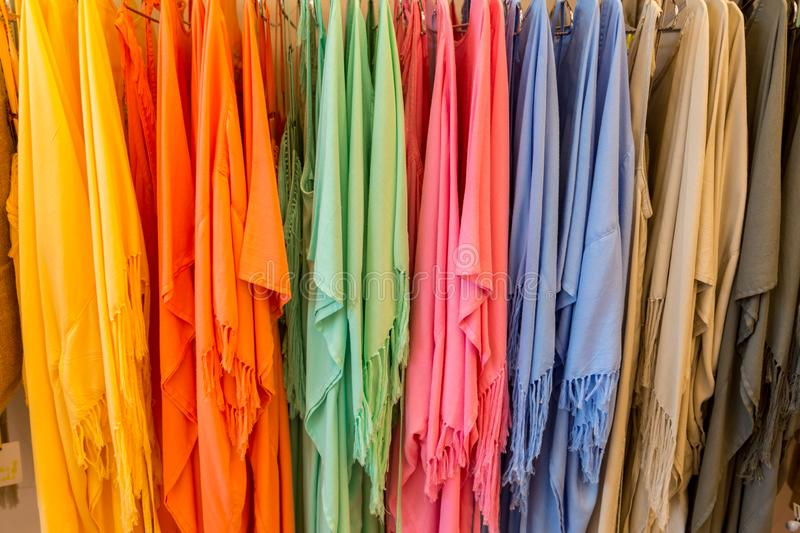 Fashion clothes on clothing rack - bright colorful closet. Close-up of rainbow color choice of trendy female wear on stock photos