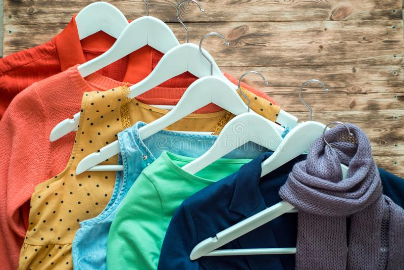 Fashion clothes on clothing rack - bright colorful closet. Close-up of rainbow color choice of trendy female wear on hangers in royalty free stock photo