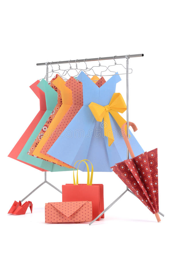 Fashion clothes: doll rack and hangers made of wire with ladies paper dresses, umbrella, purse, handbag and shoes. Isolated on white royalty free stock photo