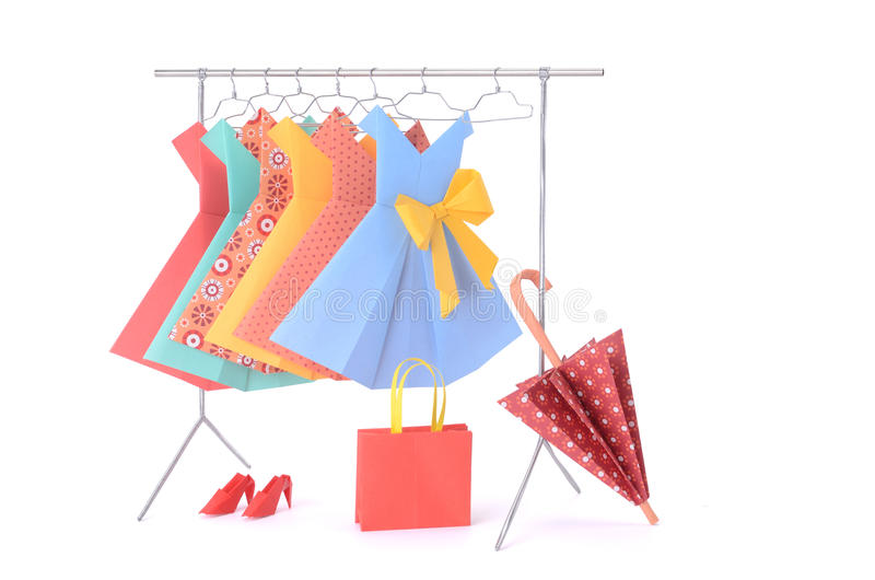 Fashion clothes: doll rack and hangers made of wire with ladies paper dresses, umbrella, purse, handbag and shoes royalty free stock photography