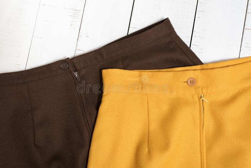 Fashion clothes. Part of brown and orange mini skirt on white wooden floor planks.  royalty free stock photos