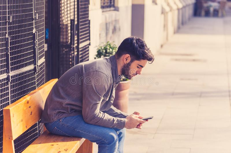 Young attractive happy stylish man on smart phone social network app in european city outdoors royalty free stock images