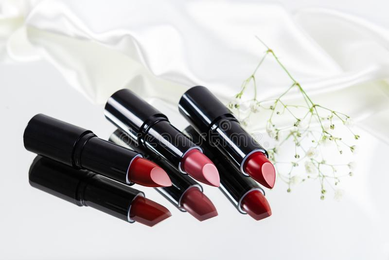 Fashion Colorful Lipsticks with reflection over white background. Lipstick tints palette, Professional Makeup and Beauty. royalty free stock photo