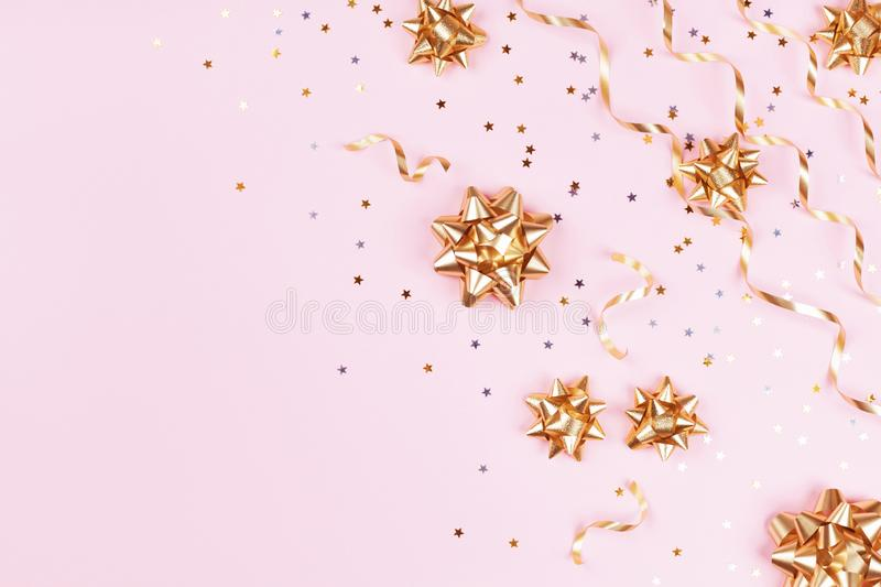 Fashion composition with golden bows, serpentine and star confetti on pink pastel table top view. Flat lay card for christmas. Fashion composition with golden royalty free stock photo
