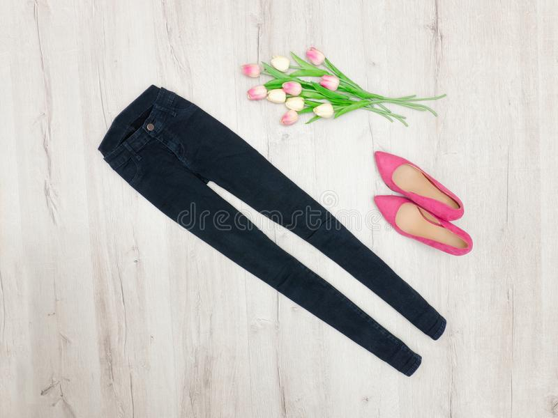 Fashion concept. Black jeans, pink shoes and tulips. Top view royalty free stock photography