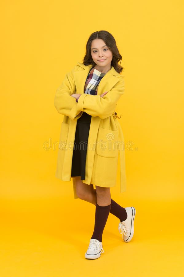 Fashion concept. Charismatic girl on yellow background. Elegant little schoolgirl. Fashionable schoolgirl. Trendy trench. Classy style. Girl adorable stylish stock image