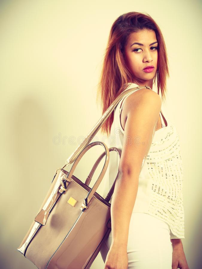 Mulatto woman holding beige leather bag. royalty free stock photo
