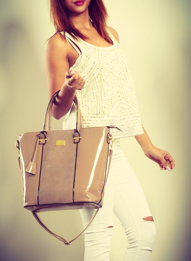 Mulatto woman holding beige leather bag stock image