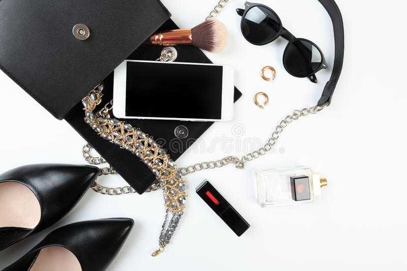 Fashion concept : Flat lay of black leather woman bag open out with sunglasses and smartphone on white background. - Image royalty free stock photos