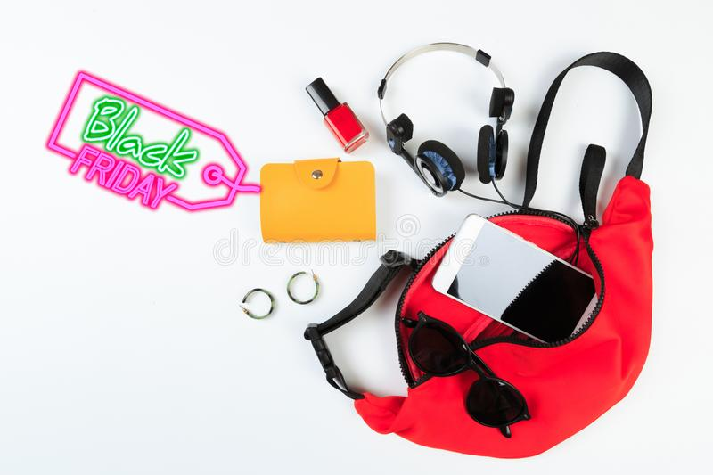 Fashion concept : Flat lay of red woman bag open out with sunglasses and smartphone on white background.- Image royalty free stock photo
