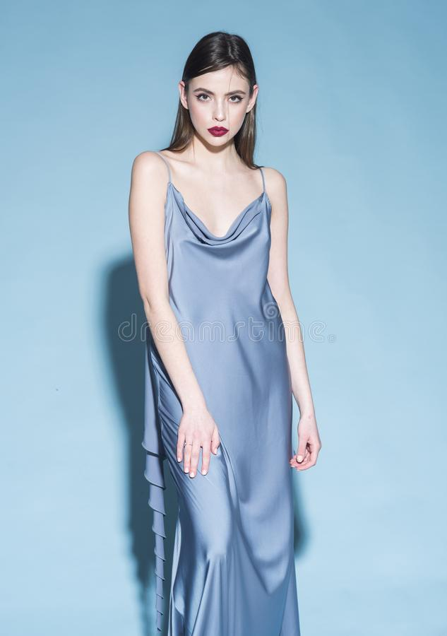 Fashion concept. Girl on strict confident face in long blue dress, light blue background. Lady with red lips looking at stock images