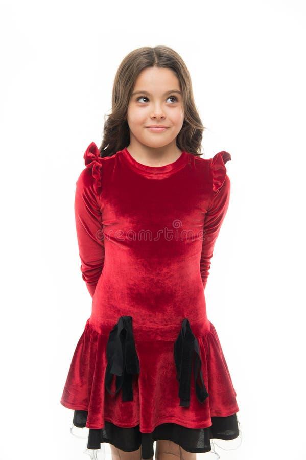 Fashion concept. Kid adorable smiling posing in red velvet dress. Kids fashion. Girl cute child wear velvet dress stock images