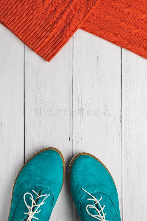 Fashion concept, top view. Casual lifestyle in autumn. Flat Lay. Green women shoes and red knitted sweater on white wood backgroun royalty free stock photos