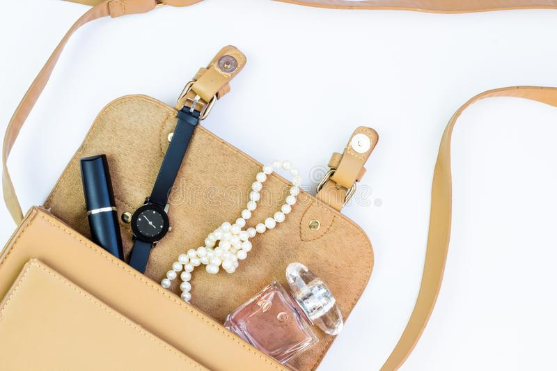 Fashion concept: women bag with cosmetics, accessories and a smartphone on a white background. Flat lay, top view.  stock photo
